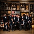 Ten men in blue velvet suits and bow ties sitting with each other and laughing with a grand bookcase in the background