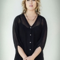 Image of Gabriela Monteri in a black shirt standing in front of a white background and staring at the camera with hands clasped at her waist.