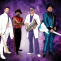 Image of the backing band for Purple Rain dressed in their various costumes standing in front of a purple background.