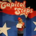 "Actor dressed up as Kellyanne Conway wearing a bright red hat and holding a sign that says ""Alternative Facts."" She is standing in front of a red, white and blue background with Capitol Steps displayed overhead"