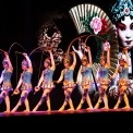 Nine women in blue costumes performing a synchronized Chinese yo-yo routine with a Chinese woman on a screen in the background