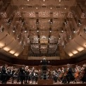 Image of Michael Tilson Thomas conducting the symphony on stage
