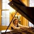 Susan Werner posed behind her grand piano looking into the camera with a tall wall and window behind her