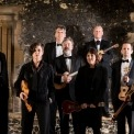 Image of the eight ukulele players holding their ukuleles standing and looking into the camera with exposed brick in the background