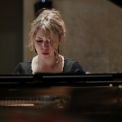 Image of Gabriela Monteri in a black shirt seated at a piano with eyes cast down toward the keys.