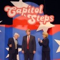 Two actors dressed up as Bernie Sanders and Hillary clinton acting upset at a third actor dressed as Donald Trump; all standing in front of red, white and blue background with Capitol Steps displayed overhead.