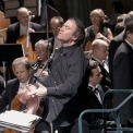Close up of a man conducting the orchestra with strings section in the background