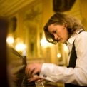 Side view of Susan Werner playing the piano with a luxurious wall behind her