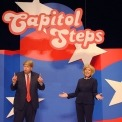 Two actors dressed as Donald Trump and Hillary Clinton debating one another in front of red white and blue background with Capitol Steps displayed overhead