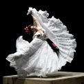 Woman in a white dress dancing on a platform with the skirt of her dress fanned out
