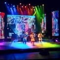 Image of the performers in RAIN on stage in colorful outfits in tribute to the Beatles of the Sgt. Pepper era.
