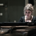 Image of Gabriela Monteri in a black shirt seated at a piano with eyes cast down toward the keys and the piano strings visible.
