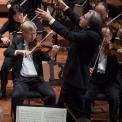 Close up and side angle of Michael Tilson Thomas conducting the symphony