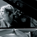 Image of Gabriela Monteri in black and white, seated at a piano glancing pensively to her right.