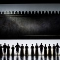 Sixteen shadowy figures standing in a line with a white and black background