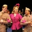 A woman dressed in a pink and black polka dot button down shirt with a black and pink hat on walks arm and arm with two soldiers.