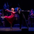 A blonde woman dressed in a red dress and red gloves dances with a man in a tux in front of the instrumentalists. She is standing on one leg in an arabesque and has her arms out.