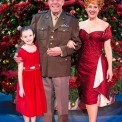 Man in uniform, woman in red dress, and young girl in red dress stand smiling in front of a Christmas Tree