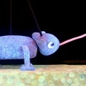 A purple chameleon puppet catching a fly with its tongue in front of a black background