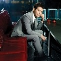 Michael Feinstein in a grey suit and tie and a white shirt sitting on a red leather couch in a dark room.