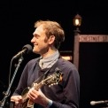 Chris Thile sings and plays mandolin wearing a collared shirt and sweater.