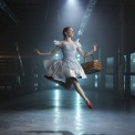 Woman in a blue dress and red shoes jumping in a room with a blue light behind her