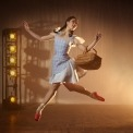 Woman in a blue dress and red shoes holding a basket jumping in front of a brown, lit up background.