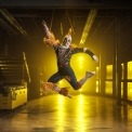 Man in a scarecrow costume jumping in a room with a yellow light in the background.