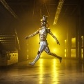 Man in a tin man costume jumping in a room with a yellow light in the background.