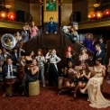 22 people in a 1920's styled room with brown, burgandy, and gold colors all variously standing and sitting. Some with instruments, some with whine glasses, all dressed in various 1920's costumes.