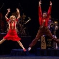 a man and woman are jumping in the air with their arms up and their legs kicked out to the sides. The woman is wearing a red skirt and a red and cream button down and the man in wearing brown pants with a red button down shirt and suspenders