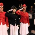 A trumpet player on the right behind a microphone plays while three ladies dressed as soldiers with white skirts salute and smile. The outer two have red tops on and the middle woman has a black top.