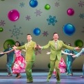 Two men in green suits dancing in front of a row of people in gray suits and red dresses dancing in front of a yellow background with ornaments and snowflakes on it