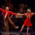 A man and woman dressed in red are dancing with their arms out while holding hands standing in front of a drum set.