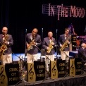 "Four saxophone players stand behind microphones and signs that say ""String of Pearls"" and play with a piano, drum, and bass player to their right also playing their instruments. An In The Mood Sign hangs above them on a black background."