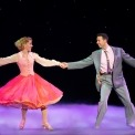 A woman in a pink dress and a man in a gray suit dancing in front of a black background