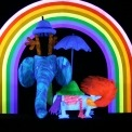 An imaginative animal puppet with an elephant head, a fox tail, a turtle back, and antlers wearing a hat and carrying an umbrella under a vibrant rainbow