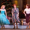 Three women dancing in a line in front of a Christmas tree