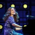 Woman in purple dress sitting at a grand piano singing in front of lights