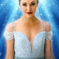 Laura Osnes in a light blue dress in front of a blue background