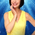 Susan Egan in a yellow dress in front of a blue background