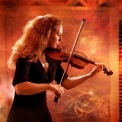 A woman in a black dress playing a violin in front of an orange background.
