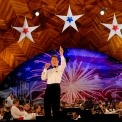 A man in a white shirt and black pants and bow tie with orchestra members playing behind him in front of a background that has a wooden roof and a screen with the American flag and red fireworks.