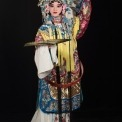 A Chinese woman wearing a headdress and robe made of ornate red, white, yellow, and blue fabric stands holding out a gold fan in front of a black background.