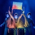 Three bald blue men dressed in black playing drums in front of a black background. Colored paint is splashing off the drums. Two of them are holding up a canvas with paint splattered on it.