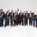 15 men, each wearing a blue suit, brown tie, and brown shoes, with a crisp white background. All men, except one, are holding a brass, wind, or percussion instrument. All of the men are smiling, some laughing.