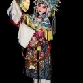 A Chinese woman wearing a headdress and robe made of ornate red, white, yellow, and blue fabric stands holding a gold fan with flowers on it at an angle near her face in front of a black background.