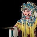 A Chinese woman wearing a headdress and robe made of ornate red, white, yellow, and blue fabric stands holding a gold fan parallel to the floor with her other hand up near her ear in front of a black background.