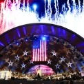 A man in a white shirt and black pants and bow tie with orchestra members playing behind him and a choir dressed in white on the left in a wooden amphitheater with an American flag and a screen with the American flag and red fireworks with real red, white and blue fireworks above the amphitheater.