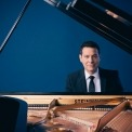 Michael Feinstein in a black suit and black tie and a white shirt sitting behind an open grand piano looking at the camera in front of a blue background.